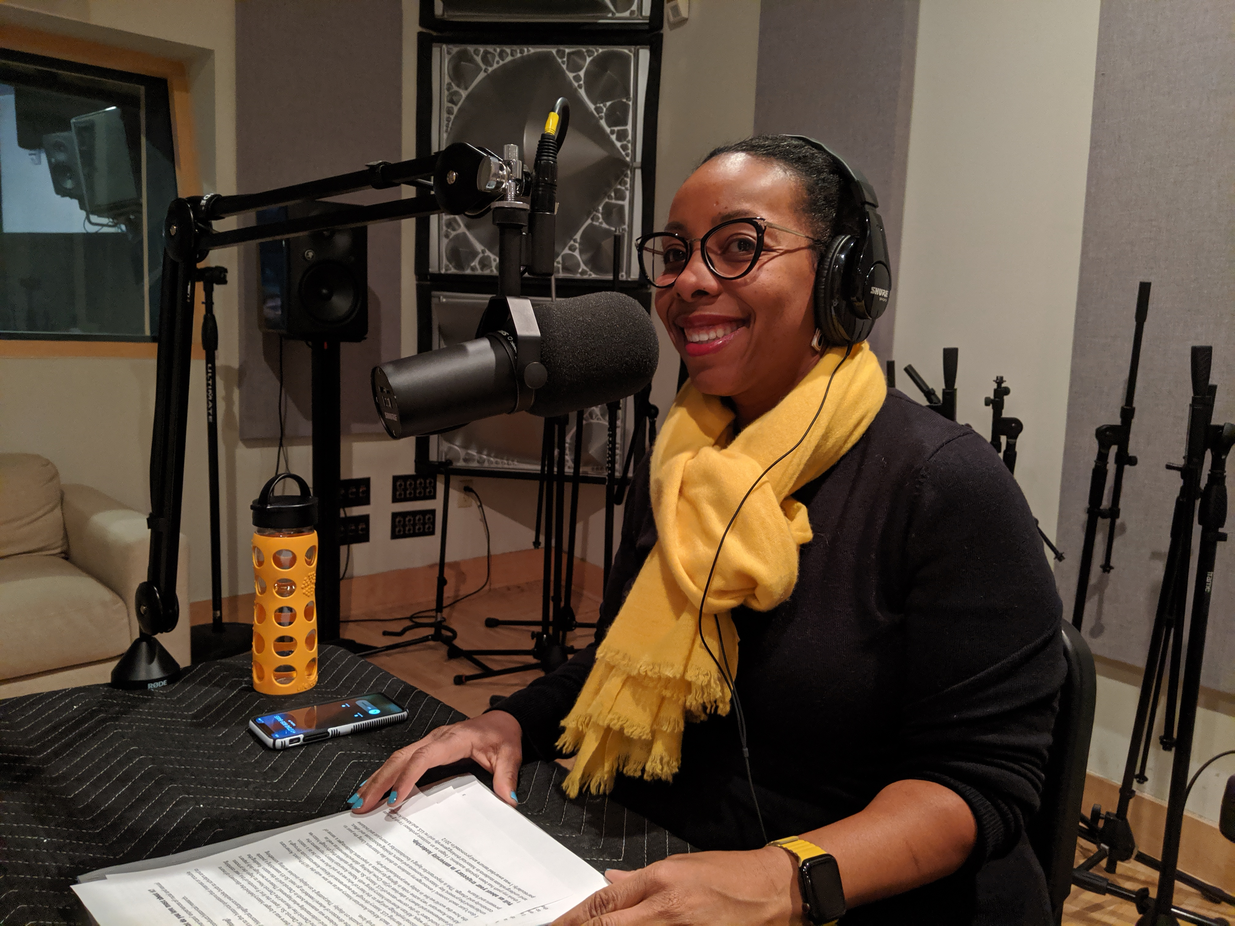 Kidada Williams in front of a microphone wearing headphones, black shirt and yellow scarf
