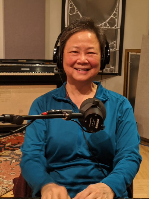 Wei-Zen Wei sitting in front of a microphone wearing headphones and blue long-sleeve blouse